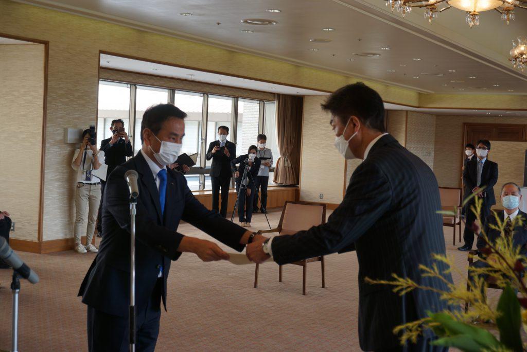 写真1.表彰する山口県知事と、賞状を受け取る中野代表取締役