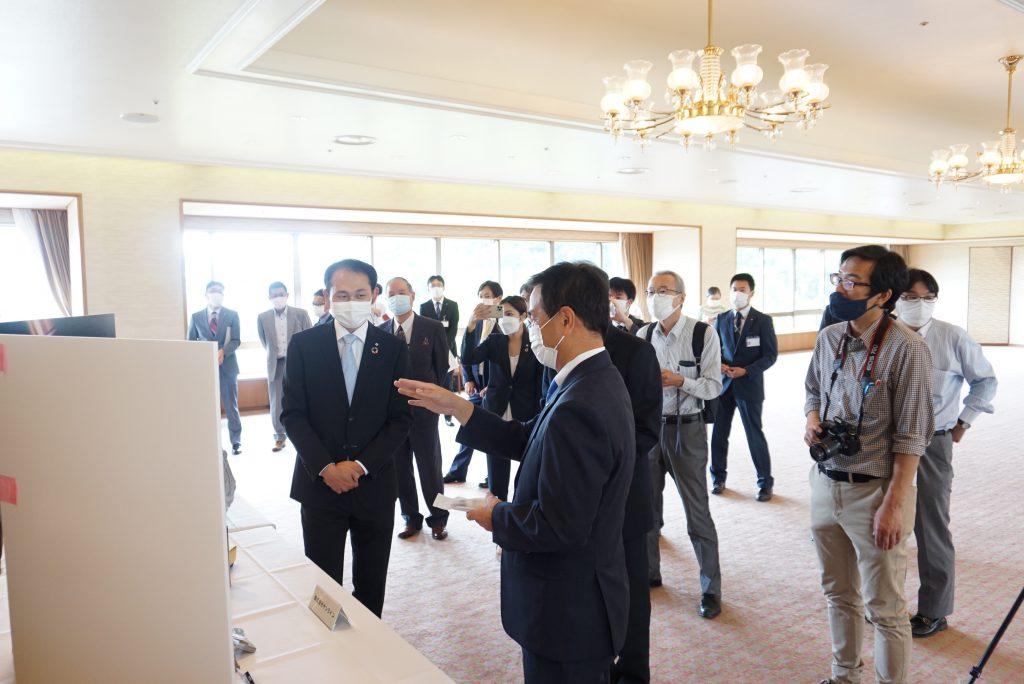 写真5.展示コーナーで村岡知事に説明する開発担当者